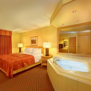 one bed guestroom with hot tub in grand ely lodge