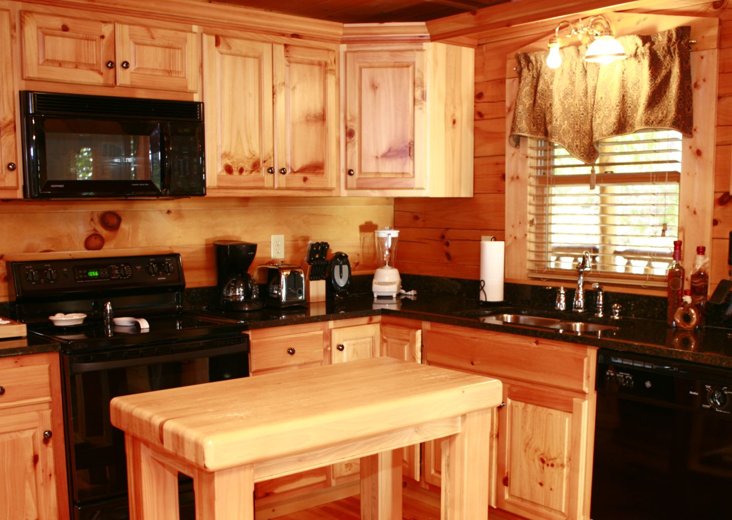A Kitchen With A Stove Top Oven Sitting Inside Of A Wooden Table